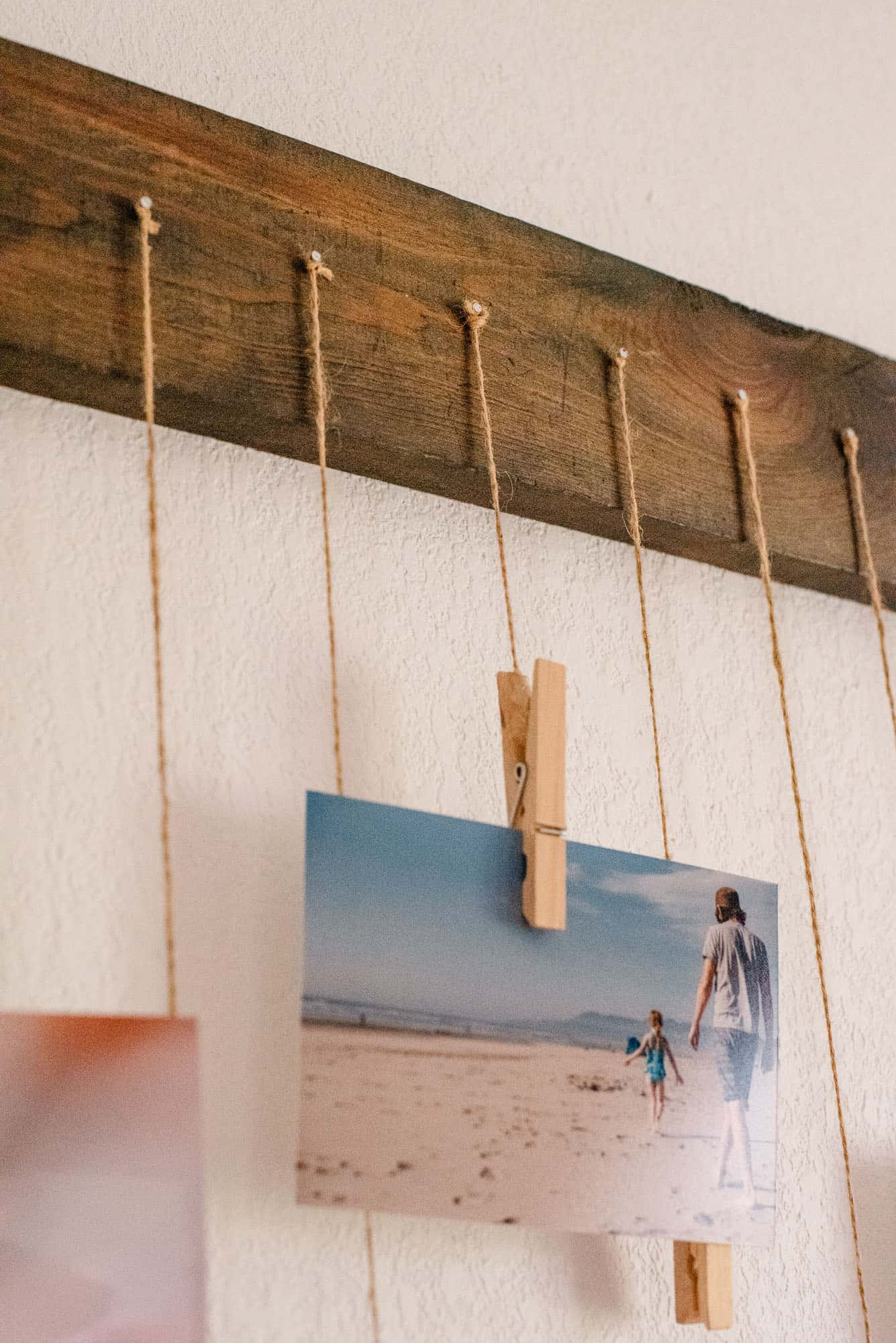 many photos hanging by string clipped on a clothes pin hanging from string on a nail on a wood board