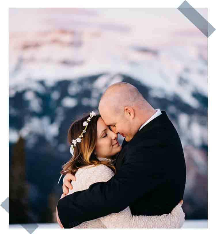 Celebrate-Again-What-To-Do-For-Your-Anniversary-wife hugging husband at the top of a snow capped mountain at sunset as the mountains are illuminated pink the couple is nuzzling noses smiling