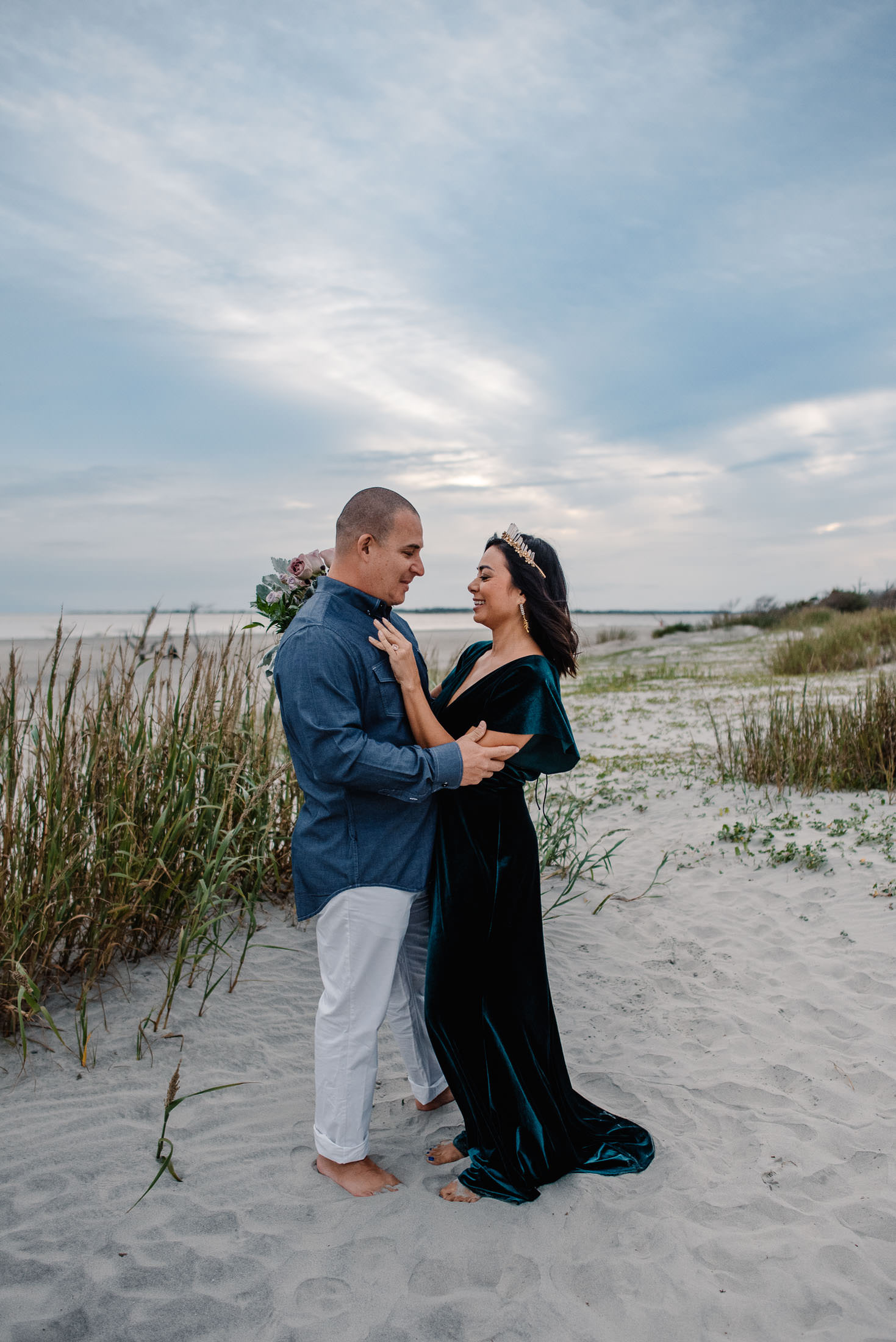Couple on anniversary trip in Folly Beach, SC standing on sand with grass near them and blue skies behind them