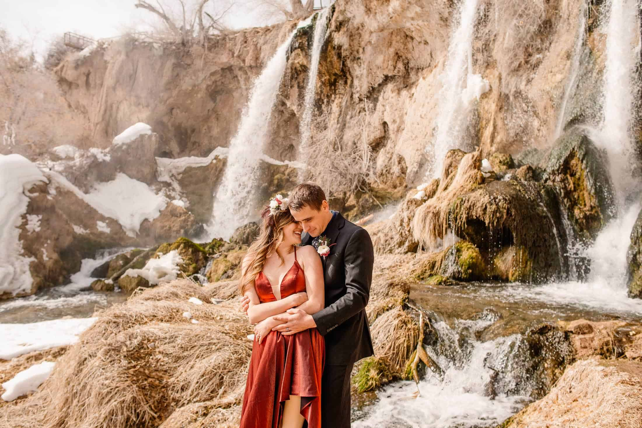 couple standing in front of waterfall after deciding on their Colorado elopement locations