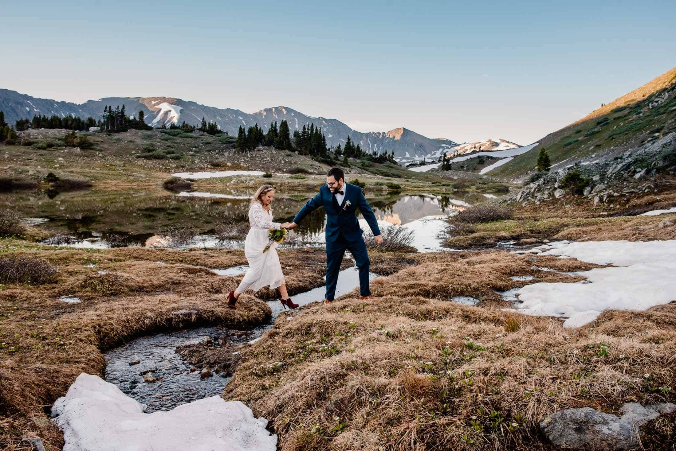 couple who decided to find the best places to elope in colorado getting married and walking over a river
