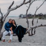couple sitting on dead tree on folly beach laughing
