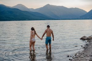 Couple playing in water in an alpine lake celebrating their anniversary