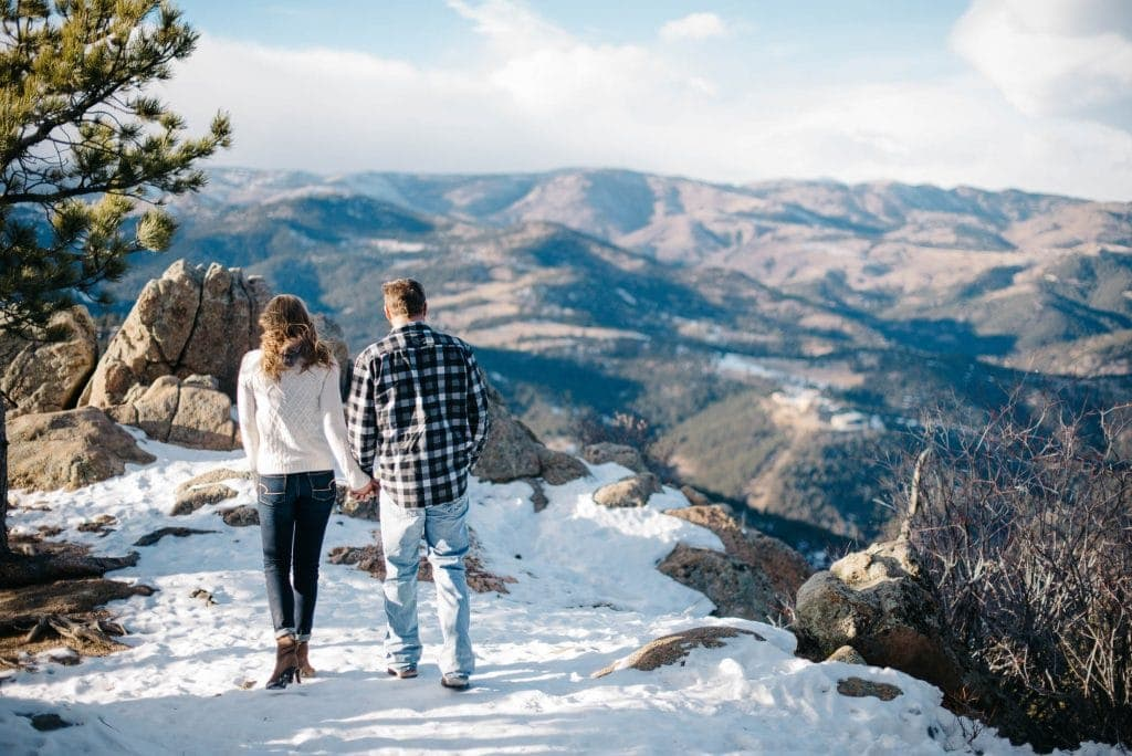 couple holding hands walking on near the edge of a cliff in Boulder, Colorado that looks out to sweeping views
