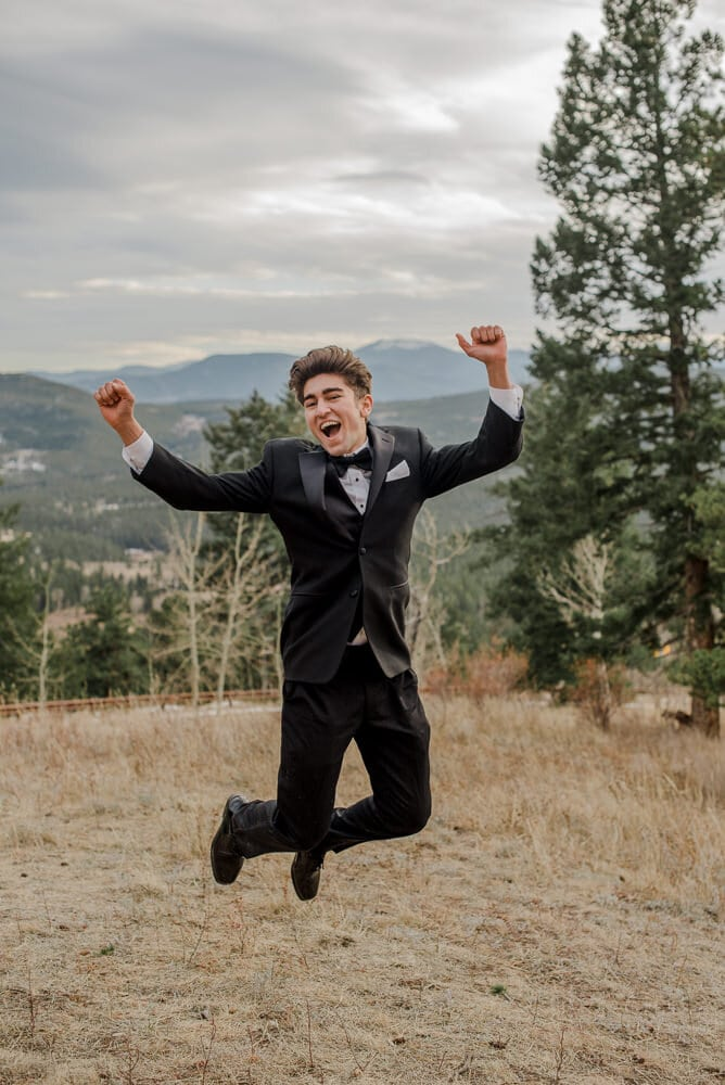 groom jumping on his wedding day in the mountains
