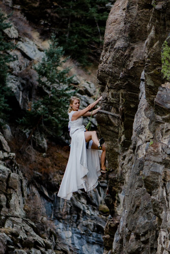 bride rock climbing in her wedding dress
