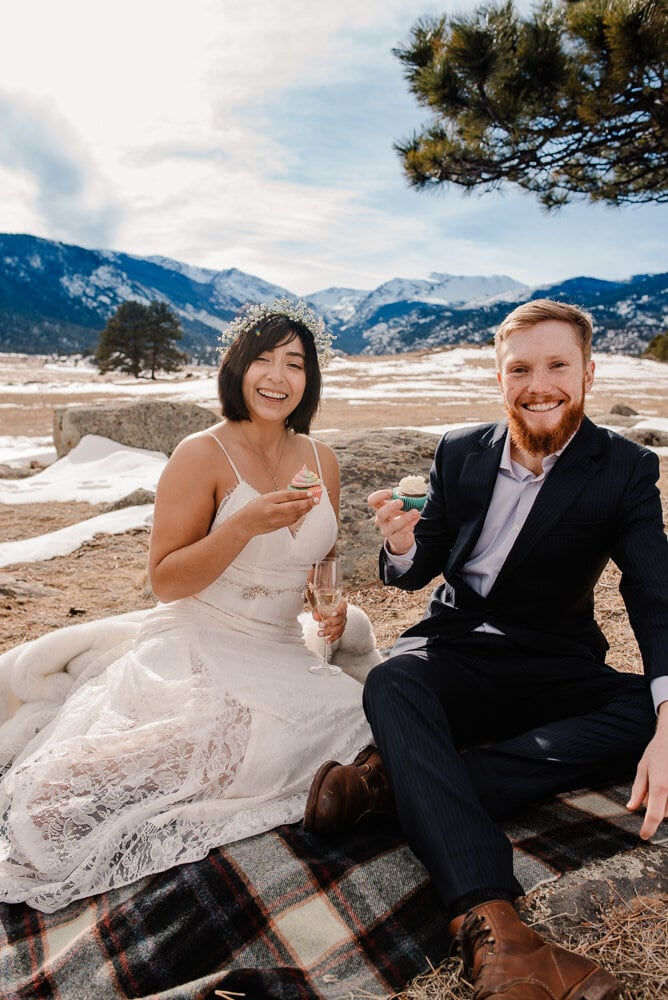 bride and groom smiling at the camera as they eat their wedding day cupcakes on a picnic blanket