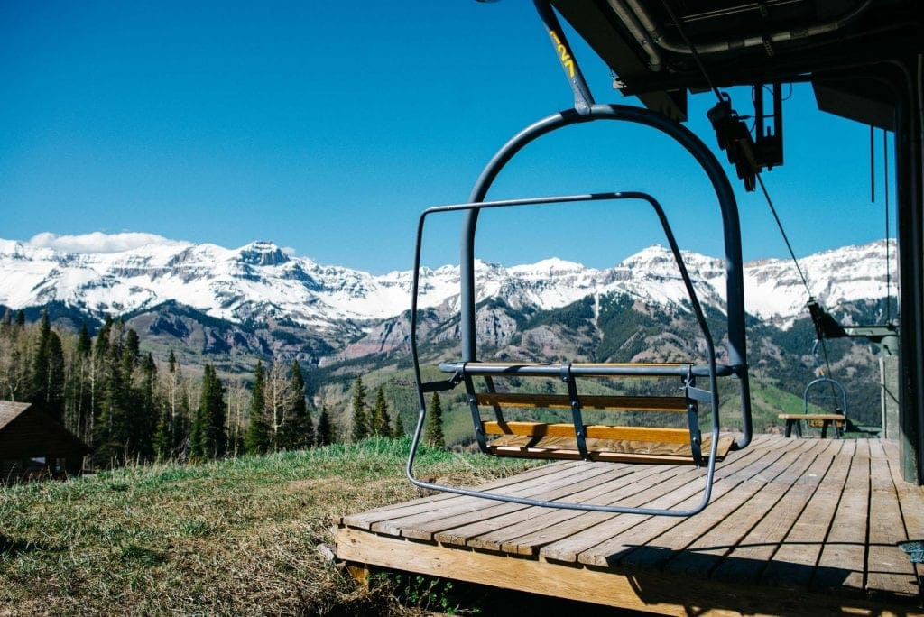 Ski lift in the summer time in Telluride, Colorado with mountains snow capped in the background