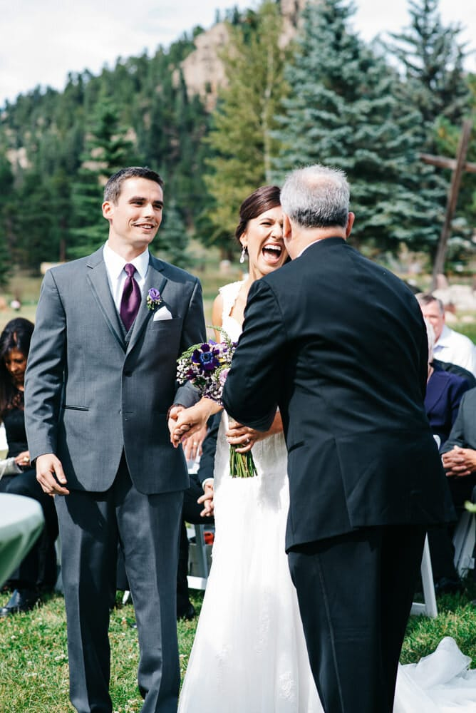 bride laughing with her dad as he walks her down the aisle