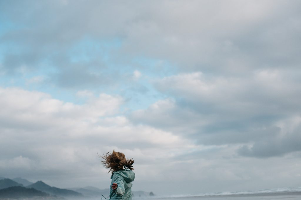 Blue skies and cannon beach mountains in background as girl in raincoat is spinning having fun