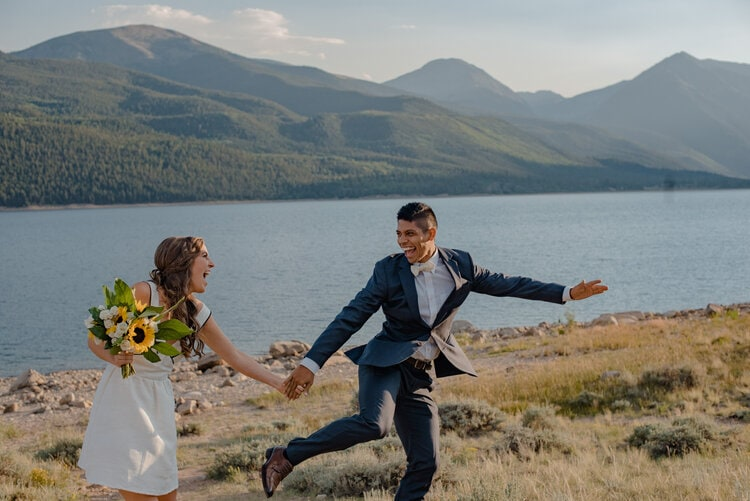bride and groom running on their wedding day in the mountains laughing