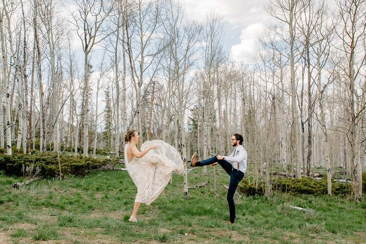 bride and groom high fiving their feet near aspen trees