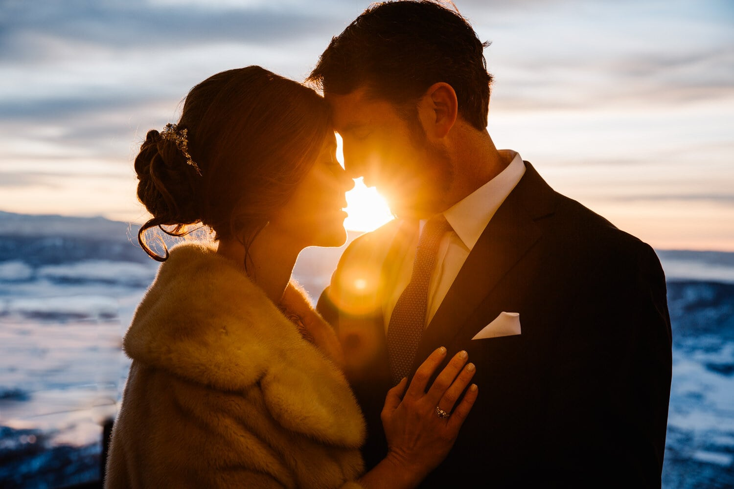 bride and groom snuggling close as the sun burst between their faces
