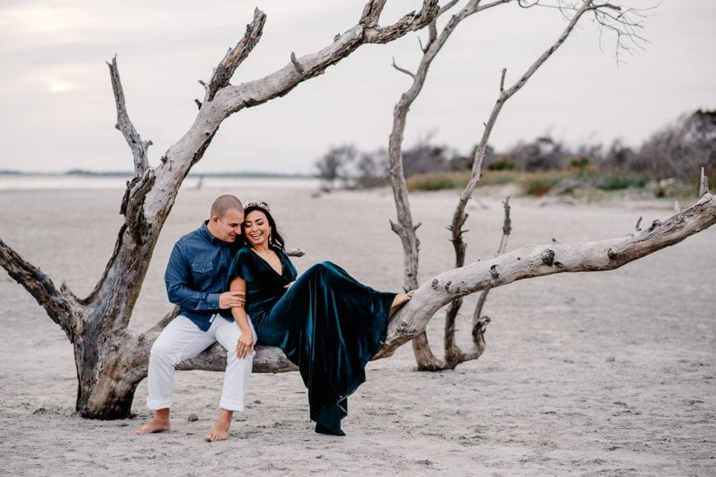 couple sitting on a dead tree off one of the beaches in Charleston, SC