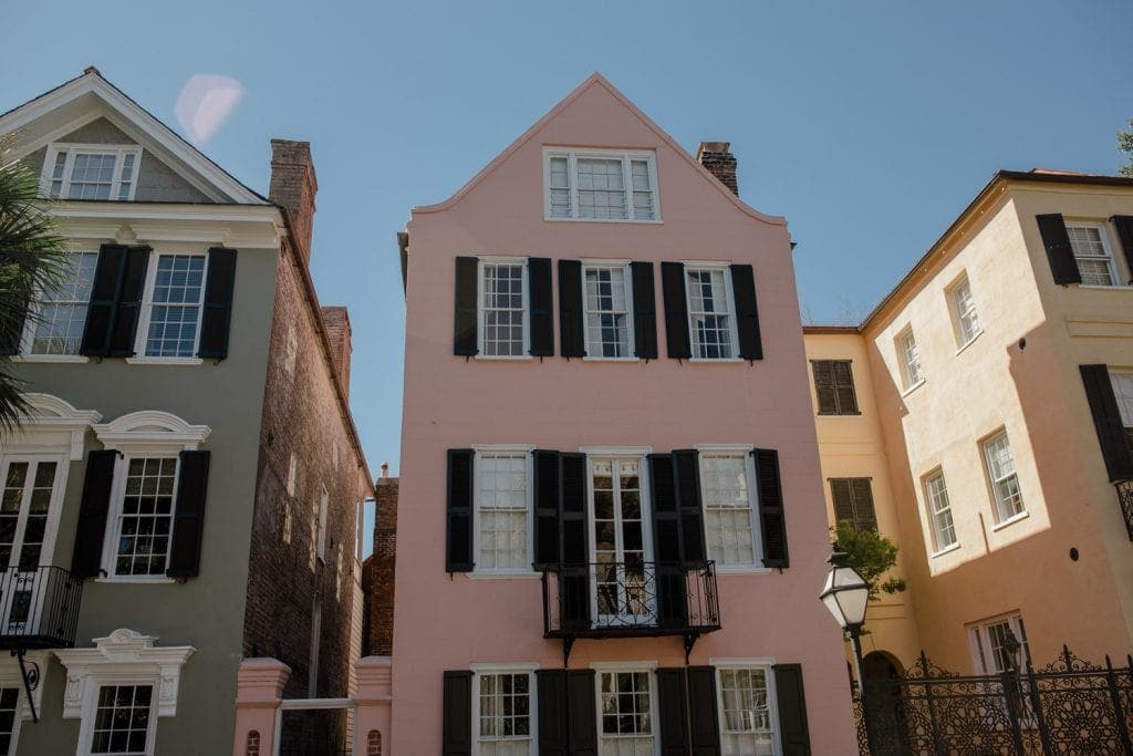 view of three of the colorful houses in charleston sc on rainbow row