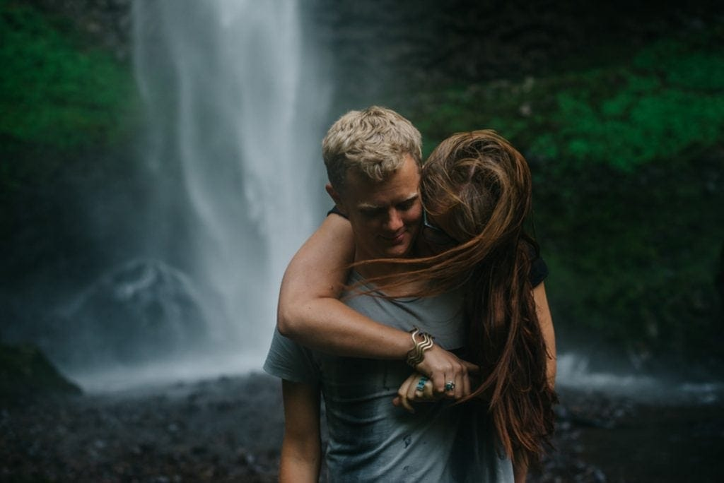 Multnomah Falls couple standing in front of waterfall with her hair wiping around his face