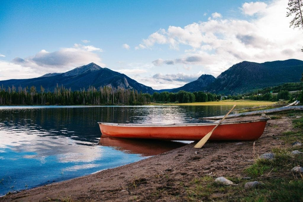 Red canoe sitting on the edge of an alpine lake