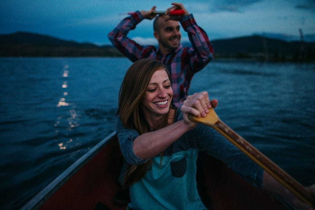 Couple on their anniversary trip in a canoe paddling as the moonlight twinkles on the alpine lake behind them