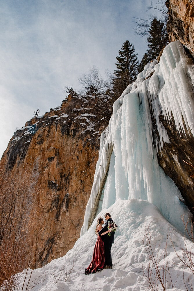 bride and groom near a froze waterfall