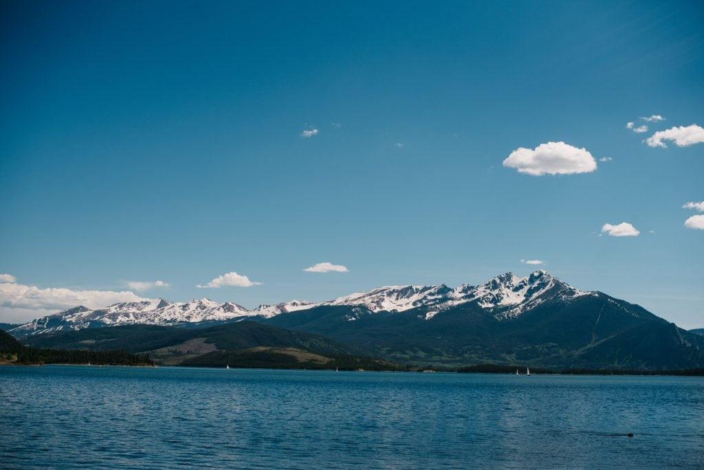 Alpine lake with mountains covered in snow in the background