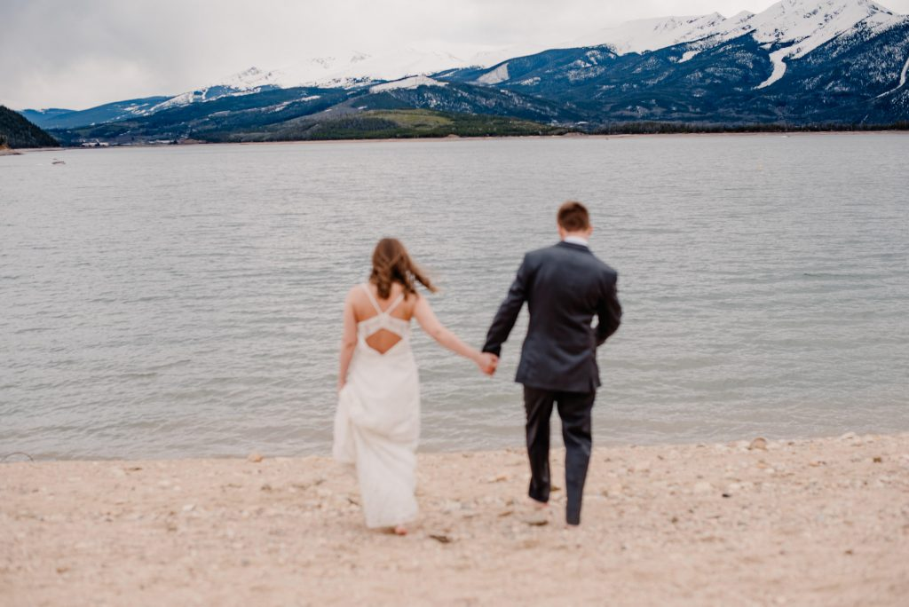 Couple on anniversary trip holding hands as they run into an alpine lake