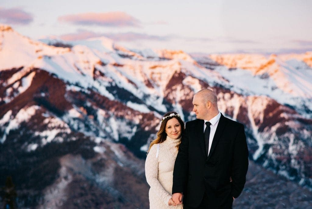 Couple on their anniversary trip in Telluride Colorado standing on the top of a mountain with the snow capped San Sophia mountains in the background illuminated pink and purple by the setting sun.