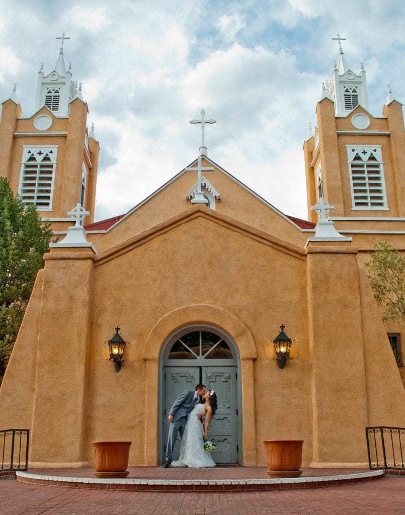 Couple on anniversary trip standing before an old southwest stucco church in Santa Fe, New Mexico