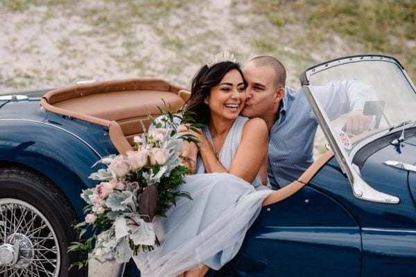 couple in a vintage car on a beach near charleston having a romantic time together.