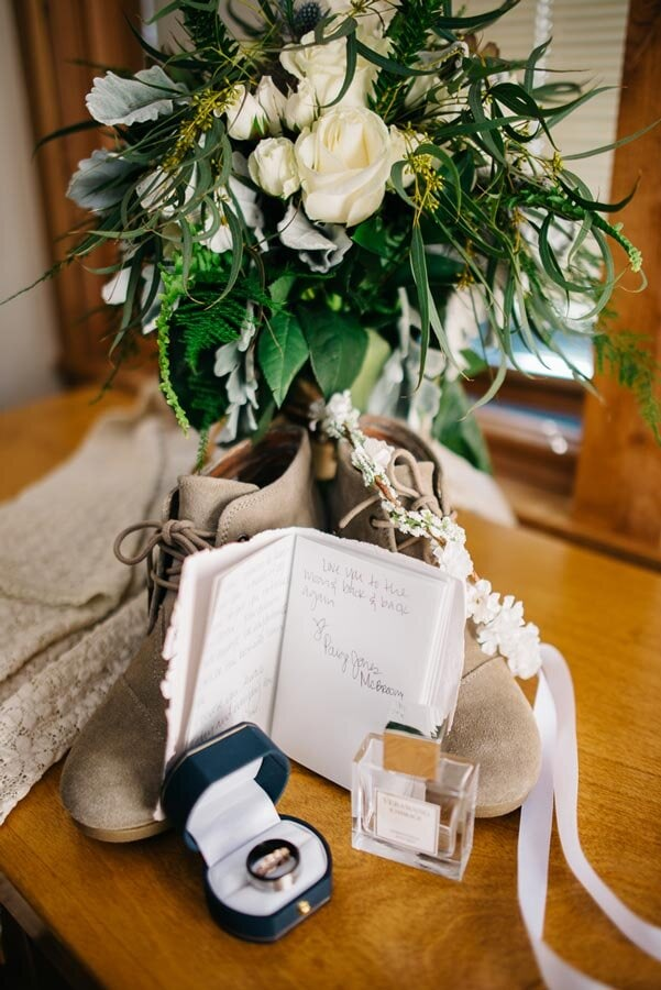 A Brides details, flowers, vow book, shoes, rings and dress that had a Sapphire Point Wedding