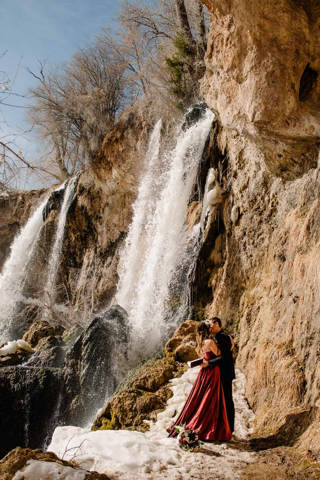 couple standing near a wedding fall on their elopement wedding day