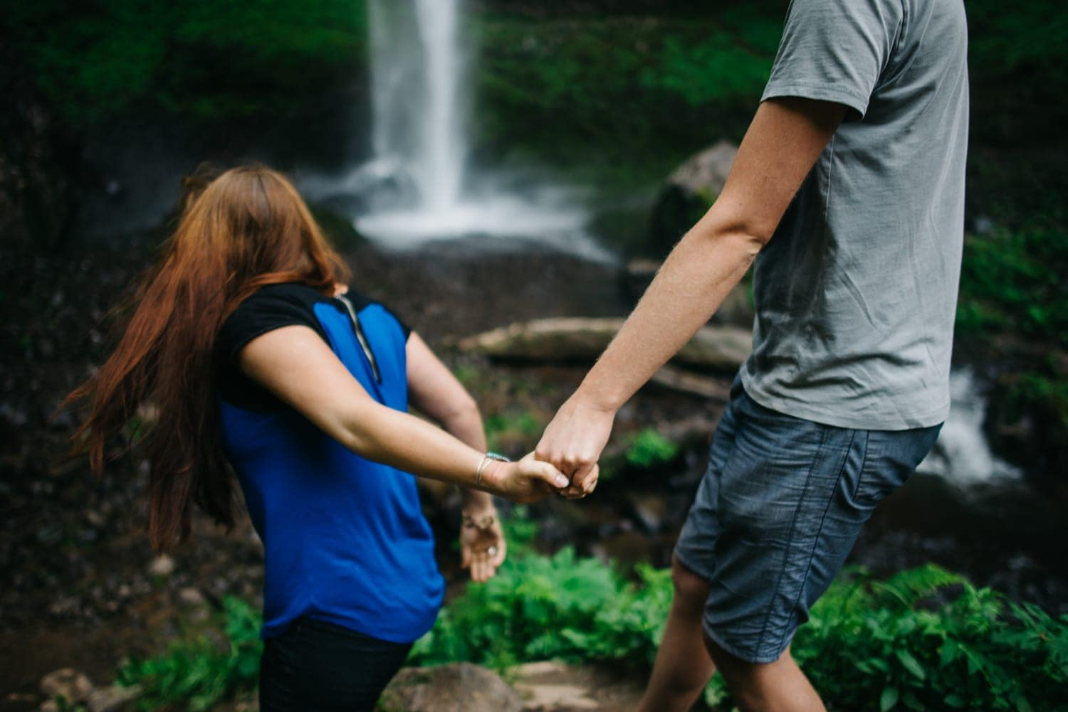 couple walking around near a waterfall holding hands