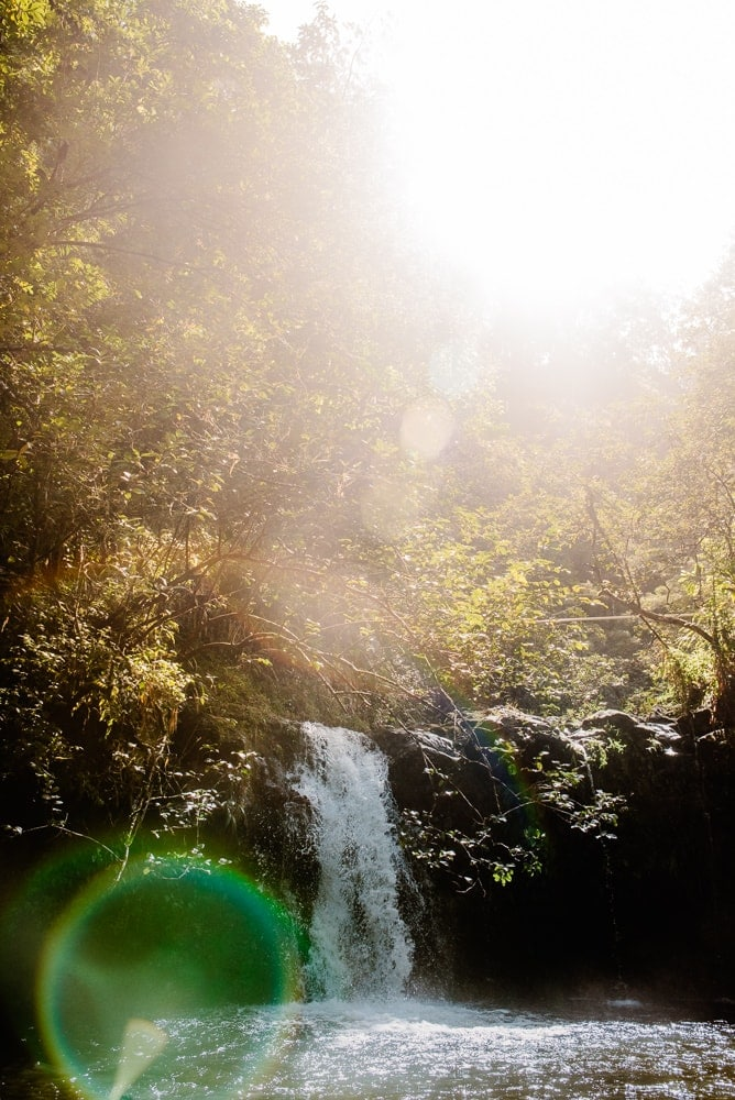water fall with the sun peaking out creating a warm color and sun flare