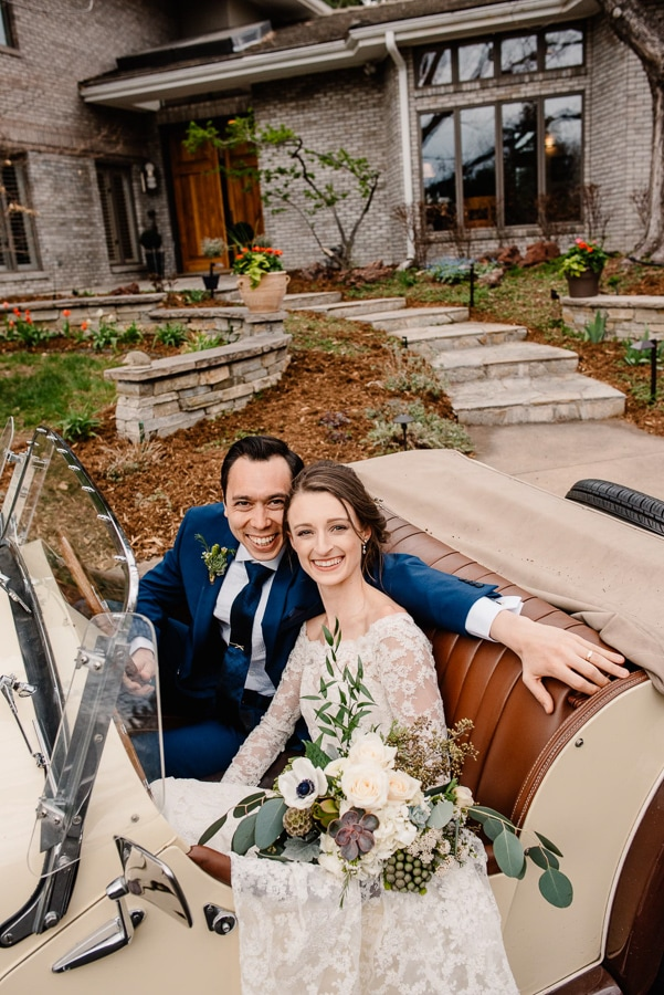 couple in backyard wedding colorado venue of an airbnb wedding colorado elopement in a vintage car smiling at photographer