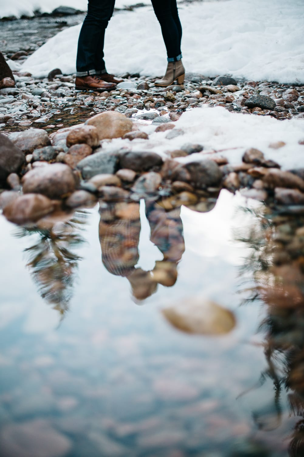 couple's water reflection in riverside during winter in Vail Colorado a good place for weddings or elopements