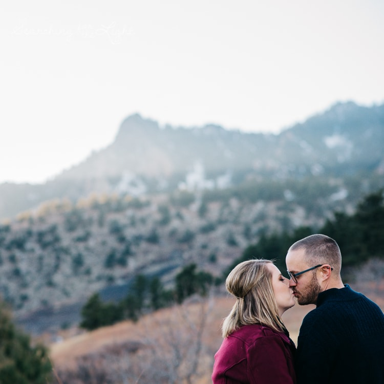 couple kissing each other as the sunsets in the mountains behind them in Colorado
