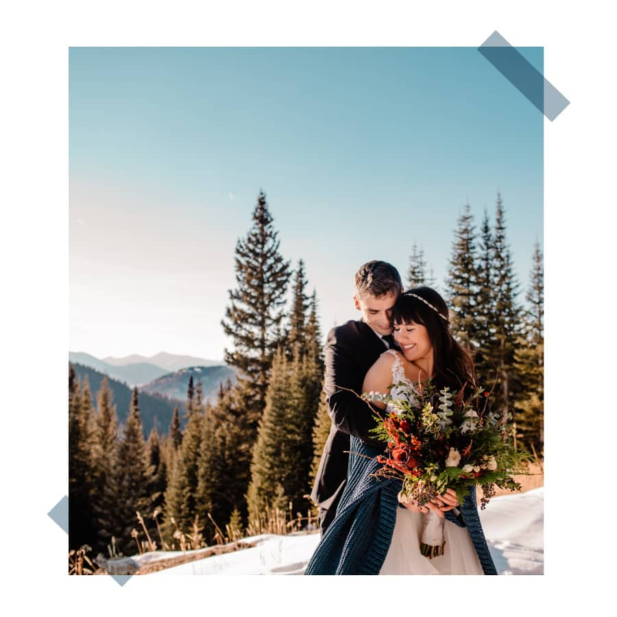 couple standing on top of a mountain from snow moibiling with their colorado elopement photographer