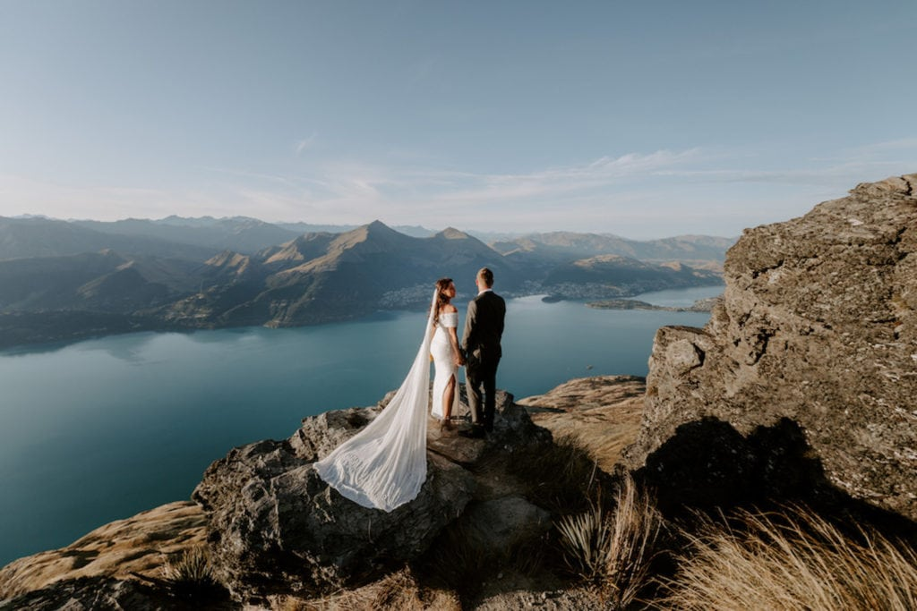 wedding couple standing on a rock over looking an alpine lake