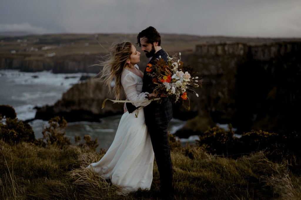 wedding couple standing on a cliff side near the ocean