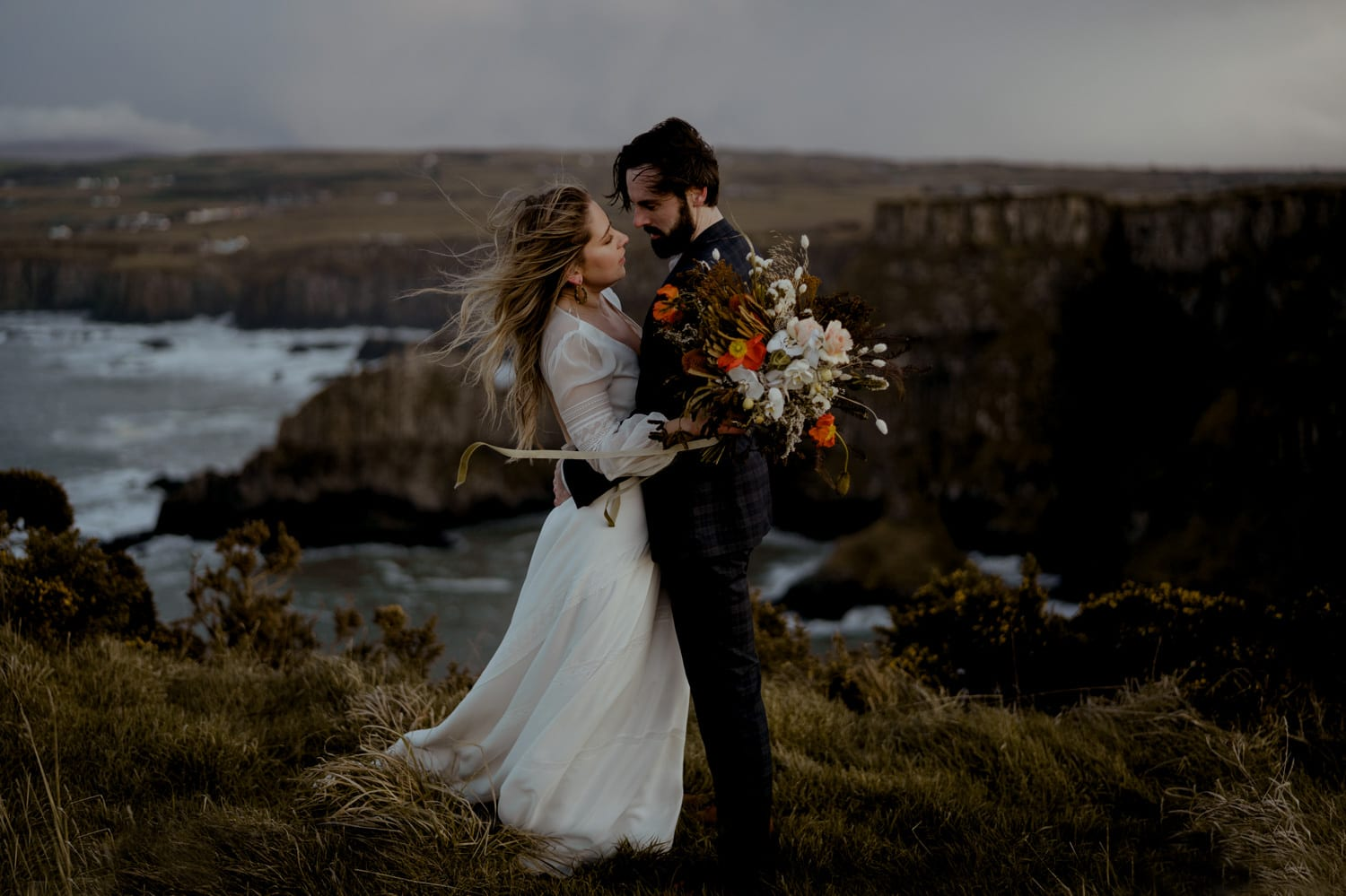 wedding couple standing on a cliff side near the ocean content because they discovered one of the best places to elope