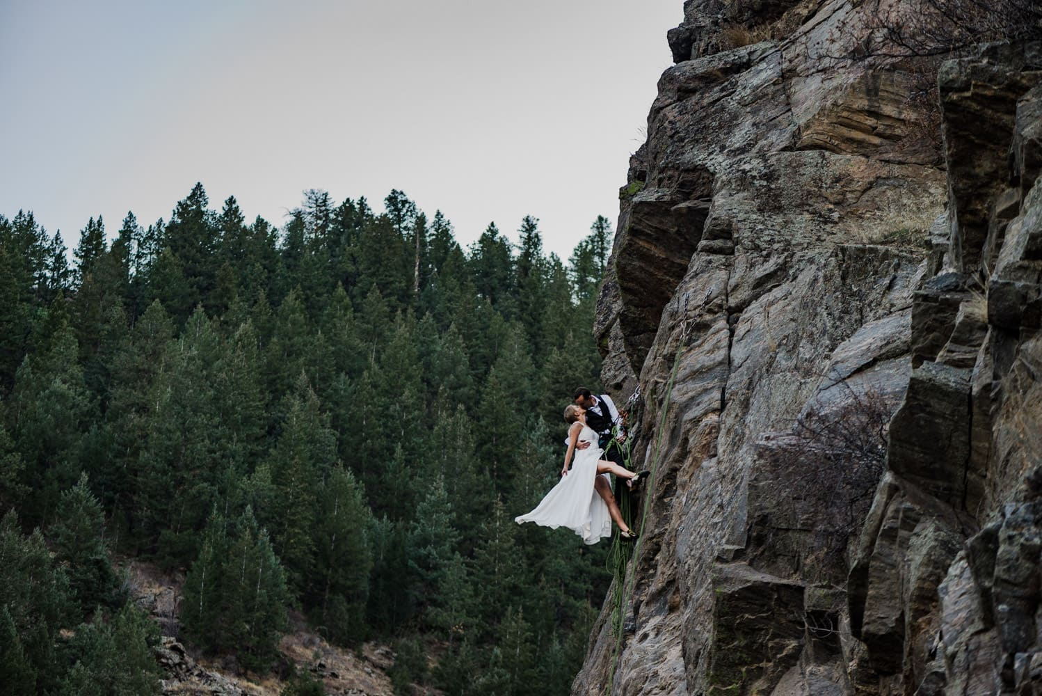 wedding couple rock climbing in wedding clothes thrilled because they discovered one of the best places to elope