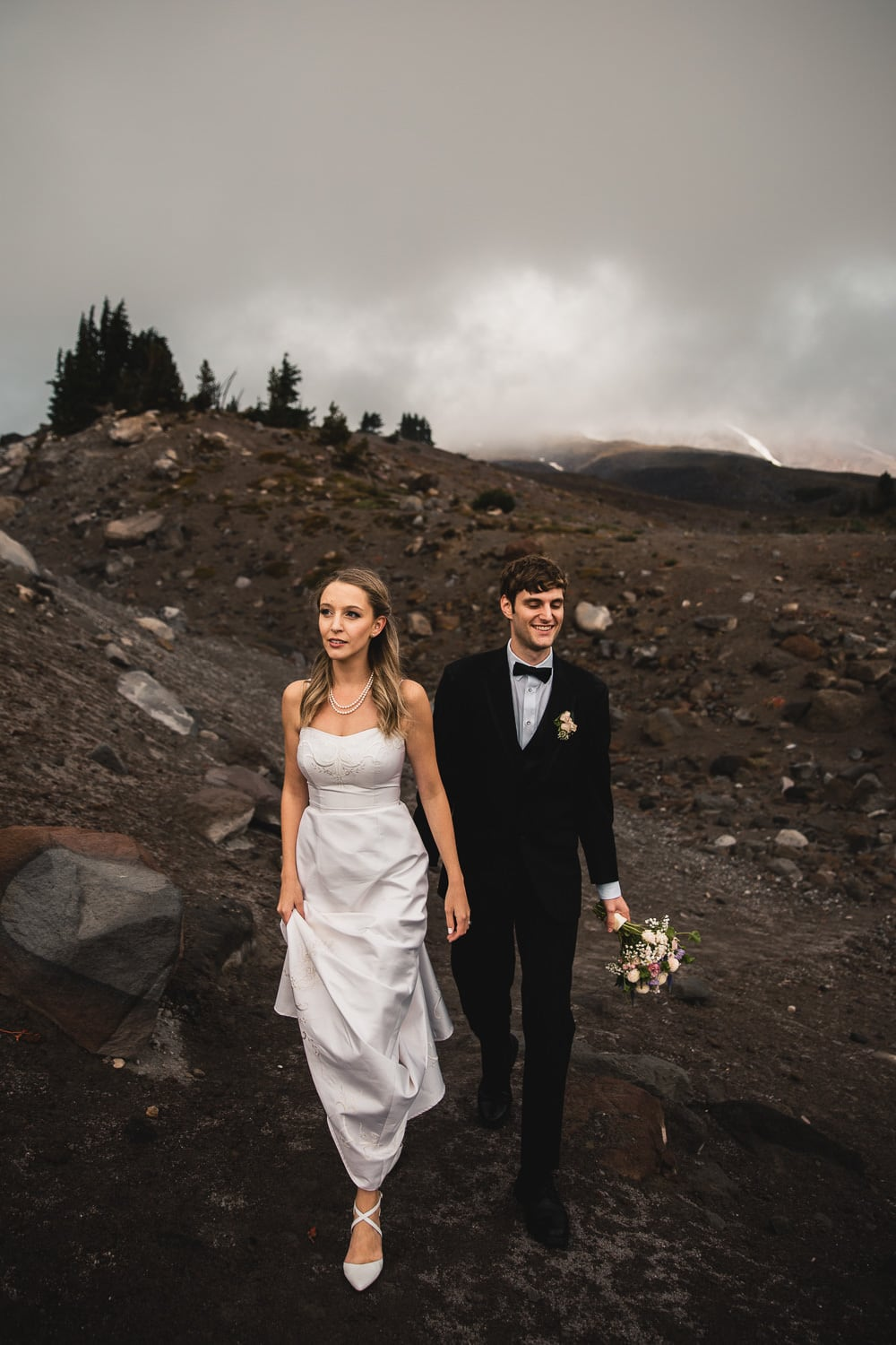 couple walking through a volcanic forest in the moody skies glad they decided on the best places to elope