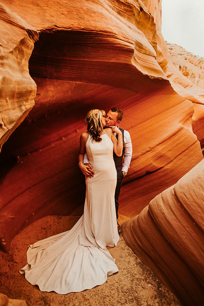 couple in orange rock kissing happy because they decided on the best places to elope
