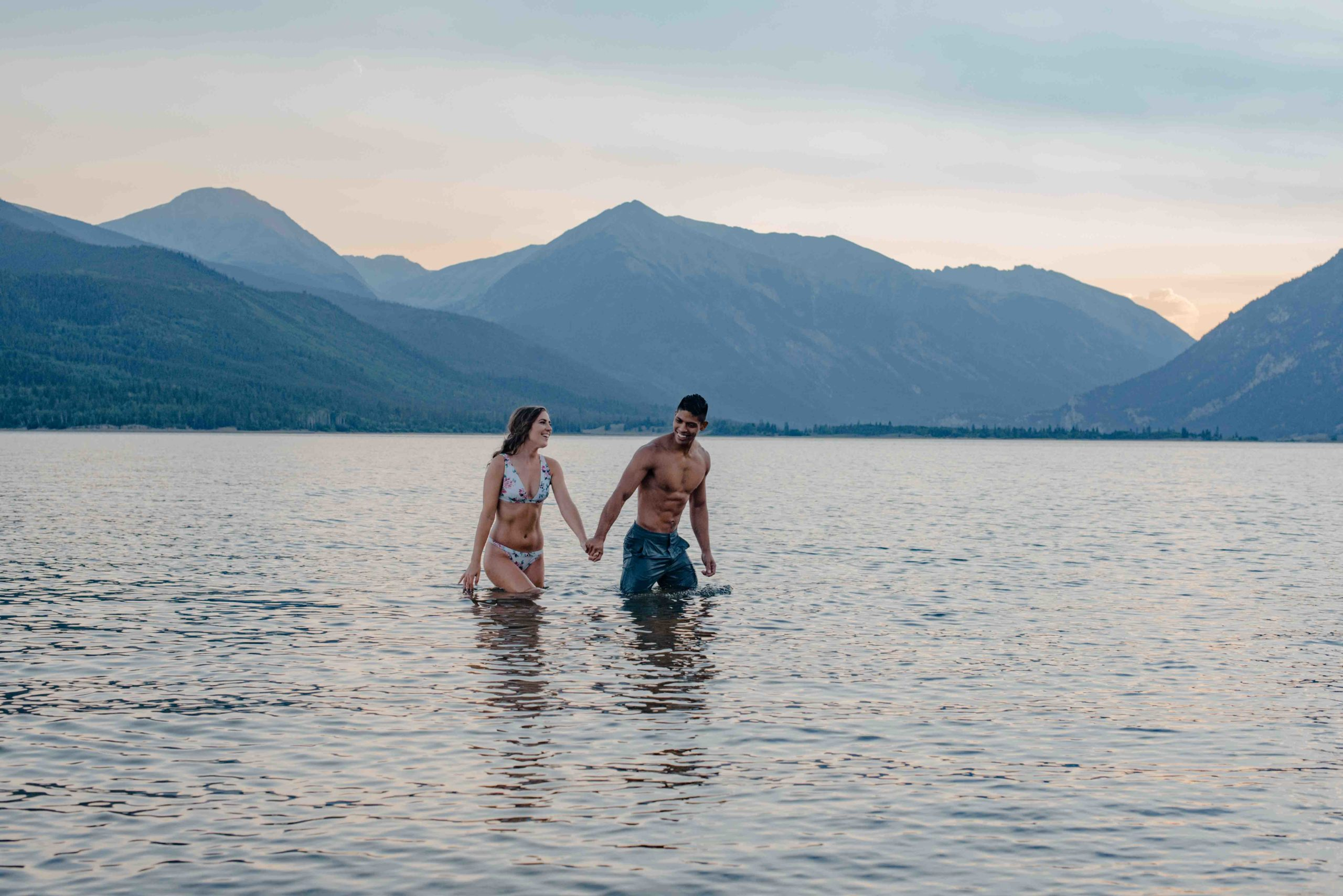 couple wadding in water near the mountains happy because they decided on the best places to elope