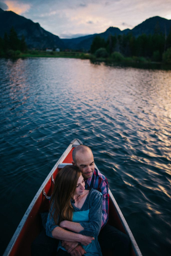 couple in a canoe at sunset on alpine lake