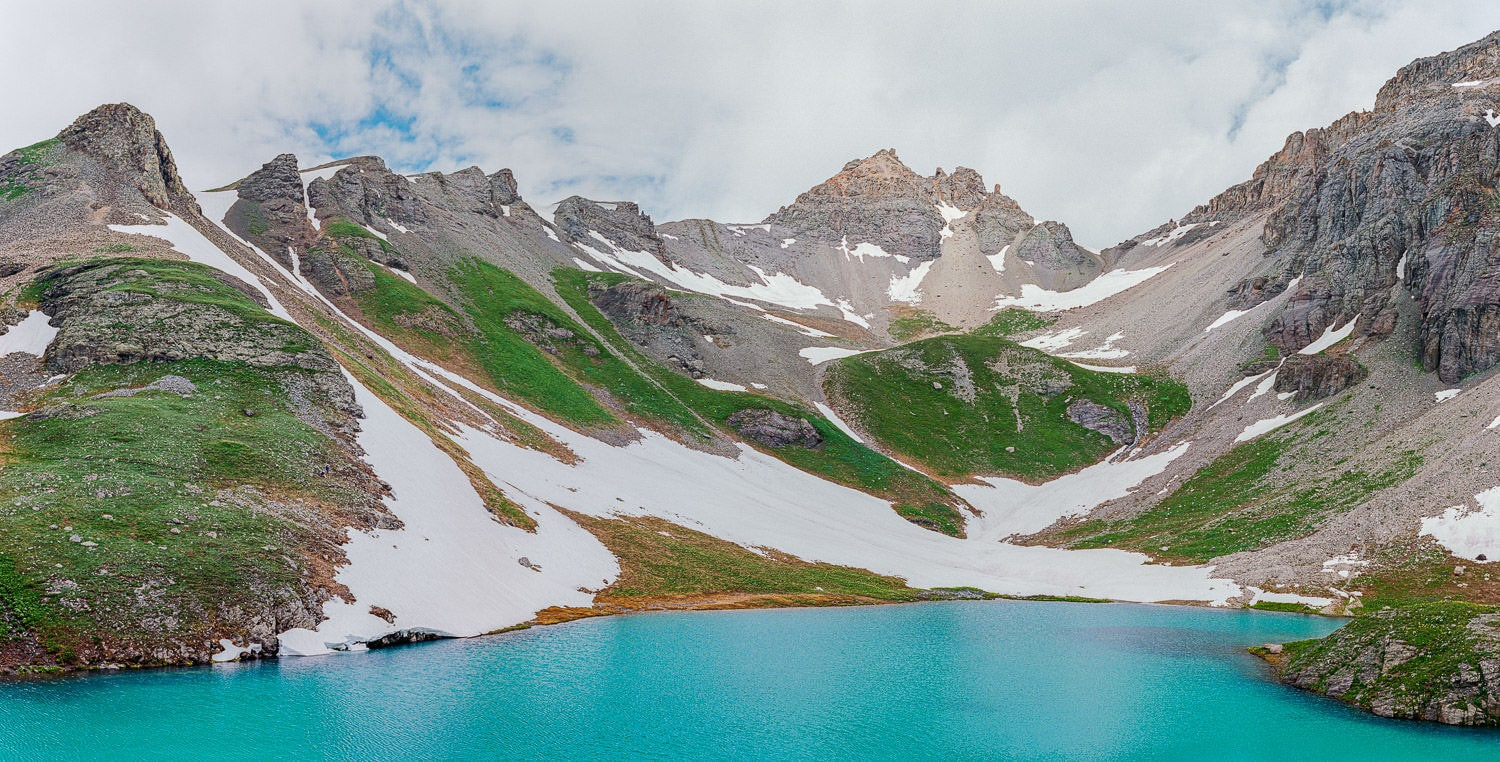 alpine lake with snow in a blue lake