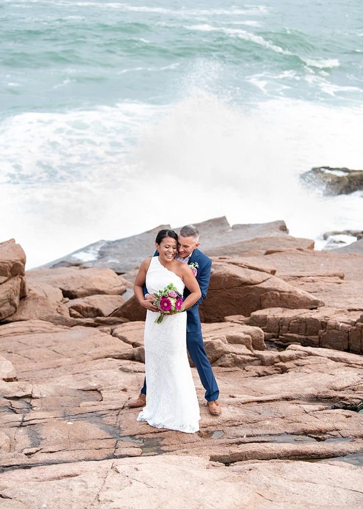 couple standing on rocks near the ocean snuggling together happy because they chose one of the best places to elope