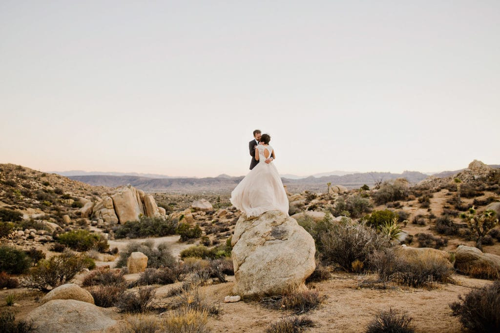 couple in the desert standing on a rock