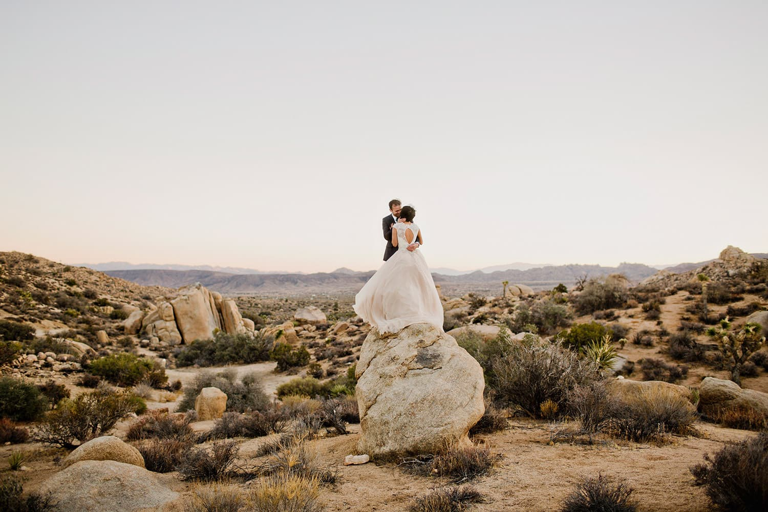 couple in the desert standing on a rock content because they discovered one of the best places to elope