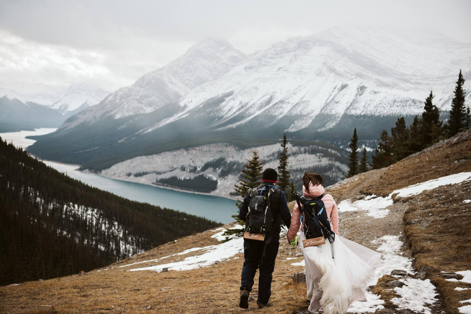 couple on mountain top over looking mountains and alpine lake with their backpacks on thrilled because they discovered one of the best places to elope