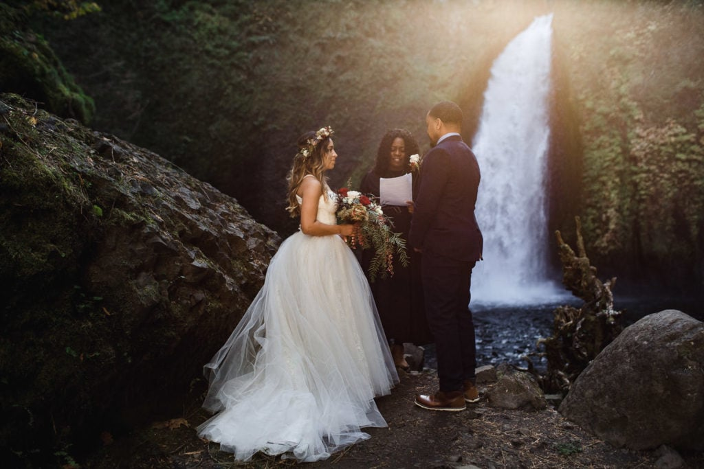 couple standing by a water fall as the sun speaks through